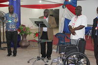 PS. B.K. MENSAH, AKIM ODA AREA HEAD A WHEEL CHAIR TO A CRIPPLE IN HIS AREA